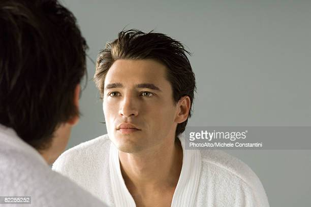 Man examining his face in the mirror, wearing bathrobe