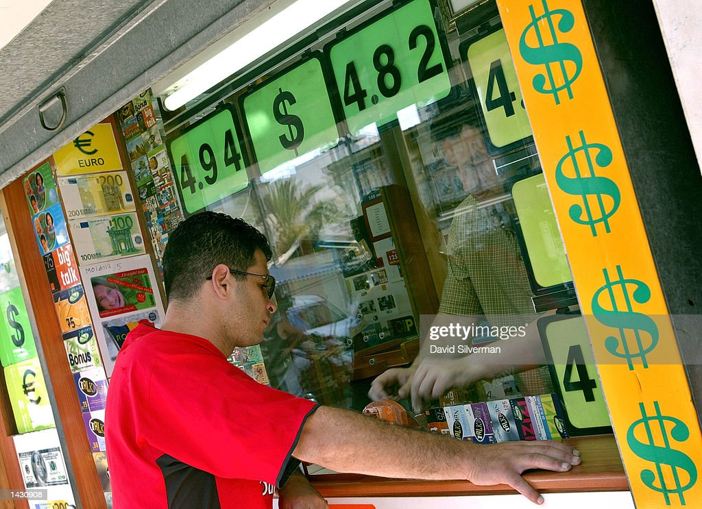A man exchanges Israeli shekels for U.S. dollars at a money changer September 25, 2002 in Tel Aviv, Israel. The buy (NIS4.82/US$) and sell (NIS4.94/US$) rates are prominently displayed on the store's signage. The shekel weakened by 1.2 percent in nervous trade to a representative NIS 4.89 to the dollar during the day, with dealers blaming the shekel's slide on growing fears of a credit rating downgrade for Israel as well as on the possible scenario of a U.S.-led attack on Iraq. Since the start of the month, the dollar has strengthened by NIS 0.23, which is a gain of 4.9 percent against the shekel.