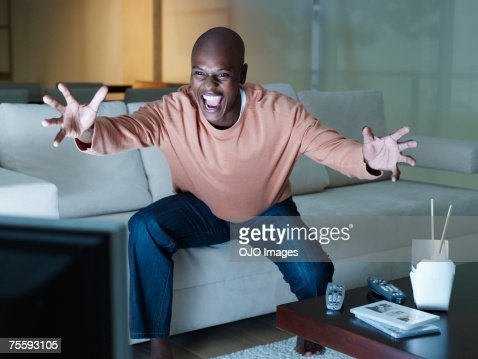 Man excitedly watching the television : Stock Photo