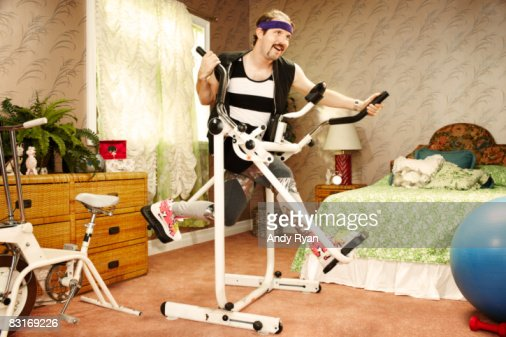 Man execising on vintage equipment in home gym : Stock Photo