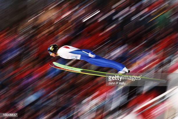 Man executing ski jump, side view (blurred motion)