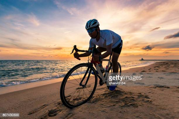 Man exercise with cycling at the summer beach in Thailand for good health and healthy medical concept.