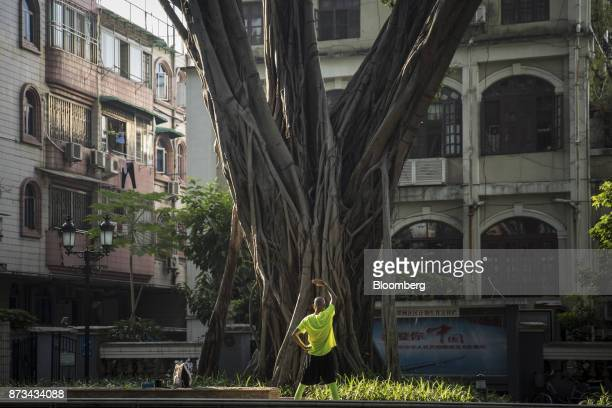 A man exercises in front of a tree on Shamian Island in Guangzhou China on Thursday Nov 2 2017 Chinais poised for an acceleration of deals as...
