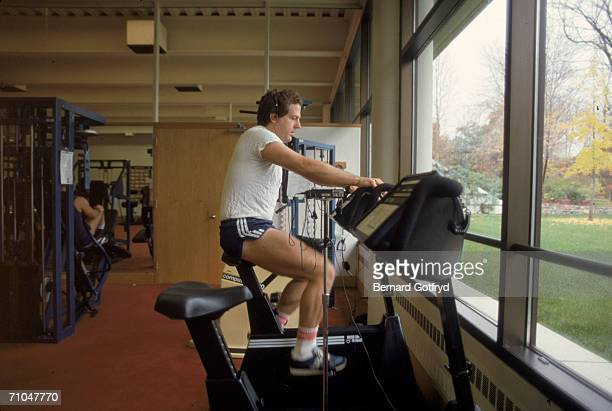 A man exercises on a stationary bicycle which faces the window in a gymnasium early to mid 1980s