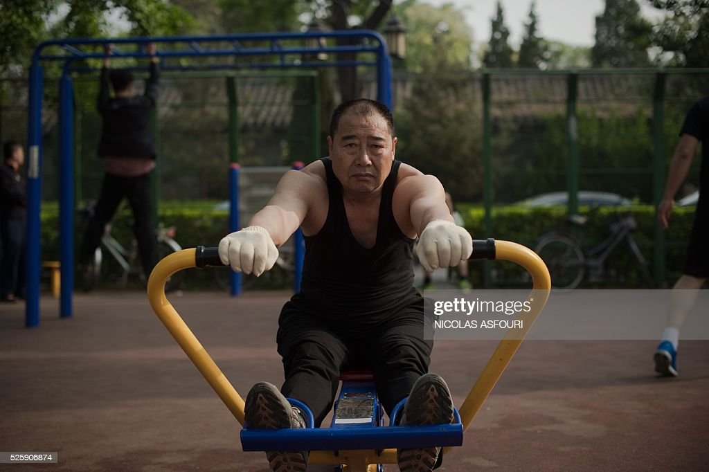 A man exercises using a rowing machine next to the Houhai lake in Beijing on April 29, 2016. / AFP / NICOLAS