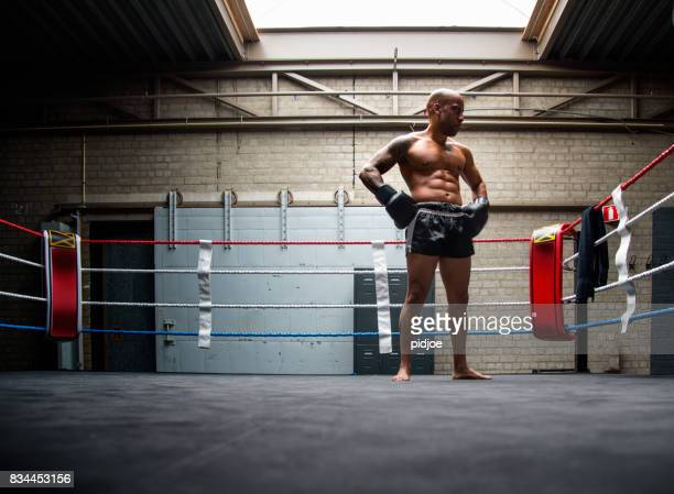 man exercising and fighting in boxing gym