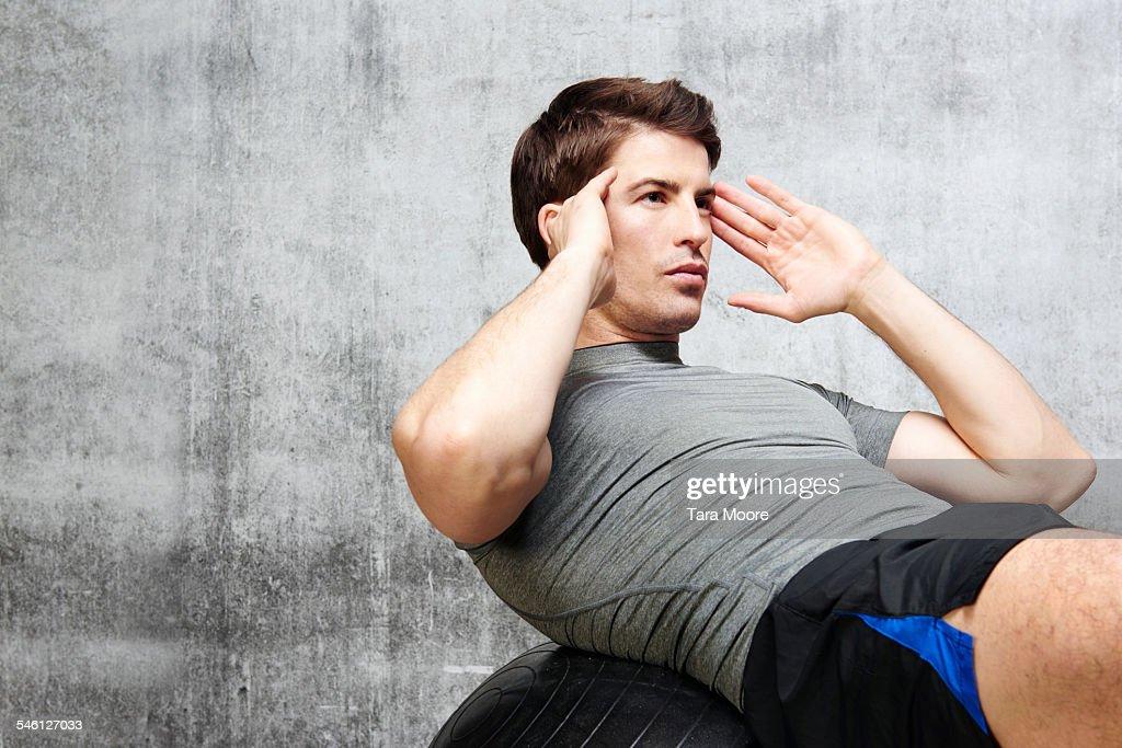 Man exercising on gym ball in urban studio setting