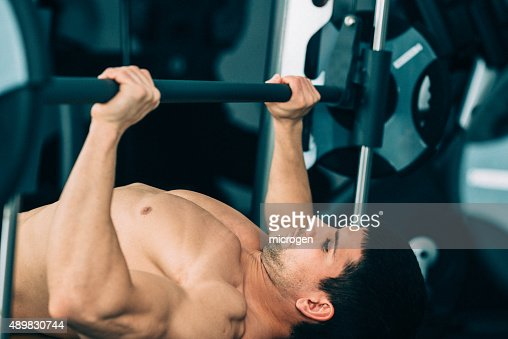 Man exercising on the bench press : Stock Photo