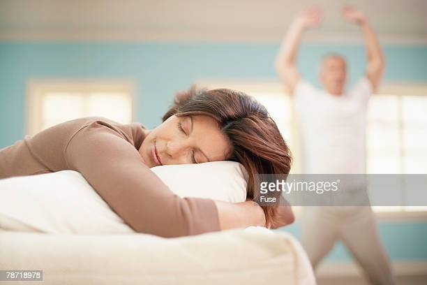 Man Exercising While Woman Sleeps