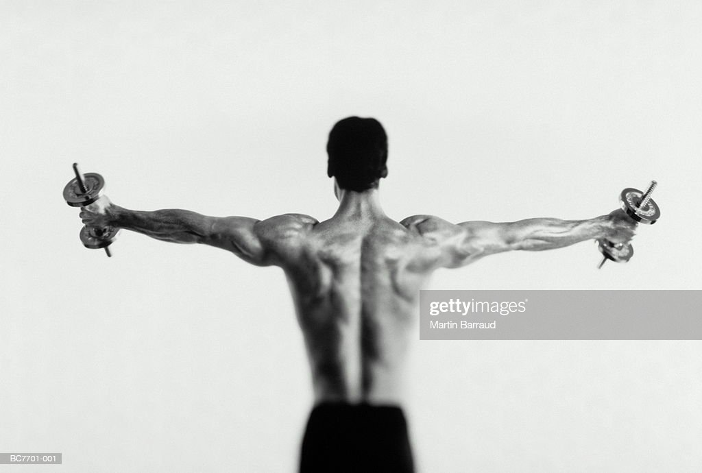 Man exercising with dumbbell, muscular arms outstretched (B&W) : Stock Photo