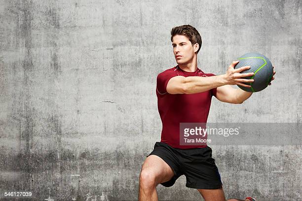 Man exercising with weight ball in urban studio