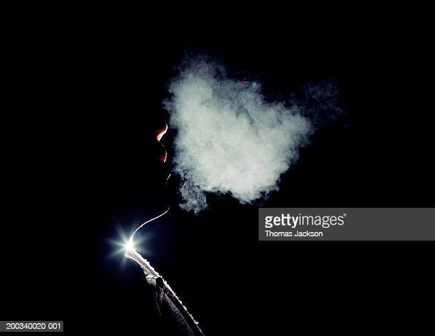 Man exhaling vapor, side view, close-up, night