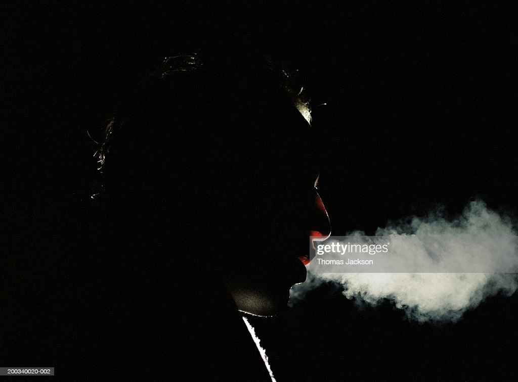 Man exhaling vapor, side view, close-up, night