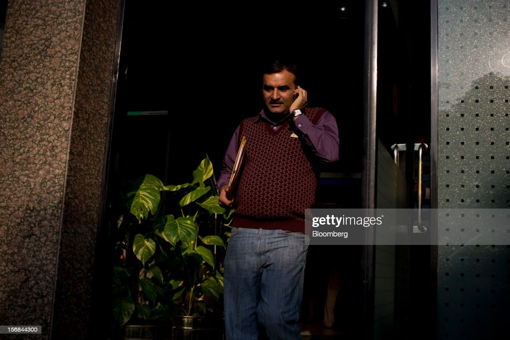 A man exits a building in Gurgaon, India, on Wednesday, Nov. 21, 2012. Indian Prime Minister Manmohan Singh aims to spur spending on infrastructure to revive a faltering economy and tackle bottlenecks contributing to one of Asia's highest inflation rates. Photographer: Brent Lewin/Bloomberg via Getty Images