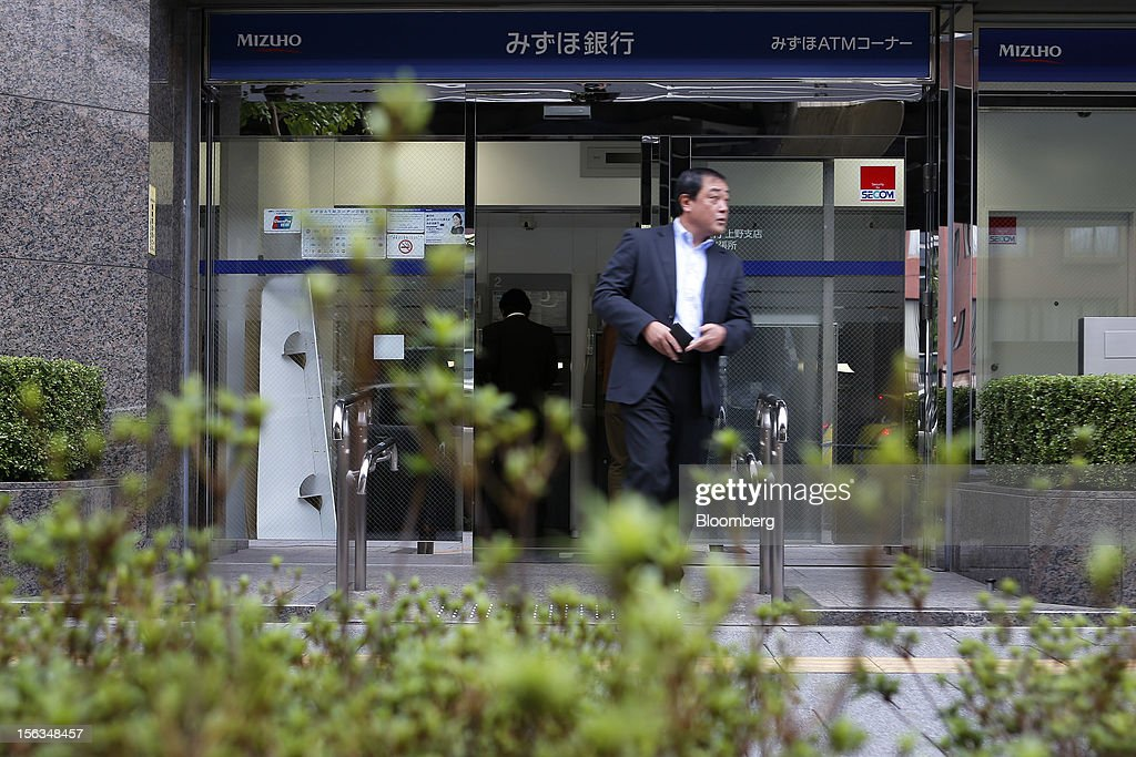 A man exits a Mizuho Bank Ltd. branch in Tokyo, Japan, on Tuesday, Nov. 13, 2012. Mizuho Financial Group Inc. is scheduled to announce first-half earnings results on Nov. 14. Photographer: Kiyoshi Ota/Bloomberg via Getty Images