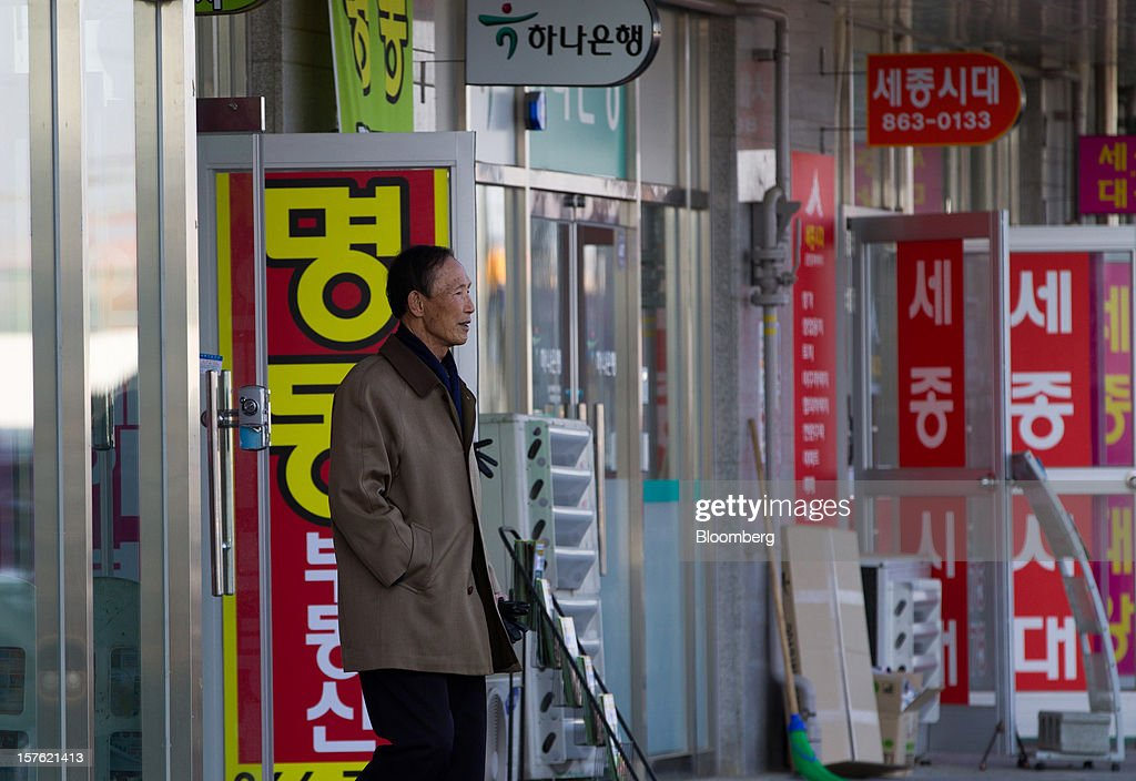 A man exits a real estate agency in Sejong, South Korea, on Tuesday, Dec. 4, 2012. The construction of Sejong City 120 kilometers (75 miles) south of the capital fulfills the vision of the late President Roh Moo Hyun, who pledged to reduce the dominance of Seoul and pump money into a region courted for its swing voters. Photographer: SeongJoon Cho/Bloomberg via Getty Images