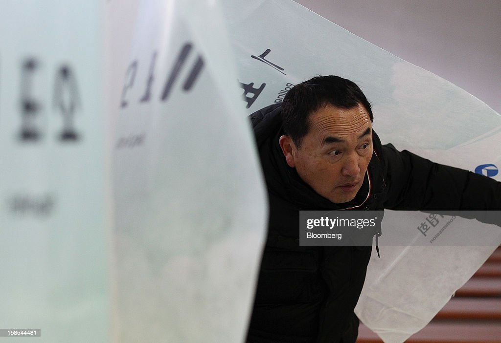 A man exits a voting booth after marking his ballot for the presidential election at a polling station in Seoul, South Korea, on Wednesday, Dec. 19, 2012. South Koreans go to the polls today to choose either a dictator's daughter or a one-time dissident as president, both of whom pledge to reverse slowing growth, a widening income gap and deteriorating North Korea ties. Photographer: SeongJoon Cho/Bloomberg via Getty Images