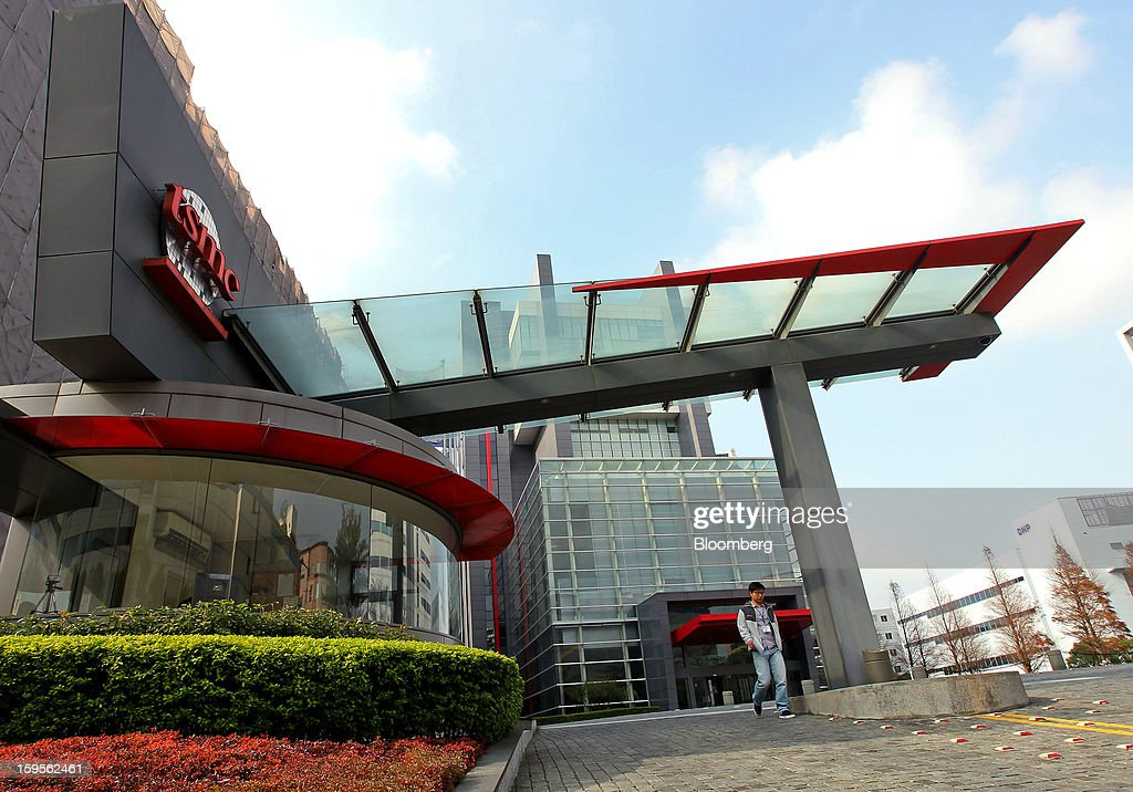 A man exits the Taiwan Semiconductor Manufacturing Co. (TSMC) headquarters in Hsinchu, Taiwan, on Wednesday, Jan. 16, 2013. Taiwan Semiconductor Manufacturing Co., the world's largest supplier of made-to-order chips, is scheduled to announce company results tomorrow. Photographer: Maurice Tsai/Bloomberg via Getty Images