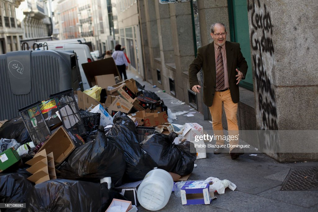 A man exlaims as he walks by garbage dumped around rubbish bins in the street on November 6, 2013 in Madrid, Spain. Street cleaners, garbage collectors and public park gardeners working for Madrid city council started an indefinite strike yesterday which was called by the trade unions. Franchise firms which employ them plan to axe around 1,000 jobs and those who will remain will have to face working for a 40 percent cut of their wages.