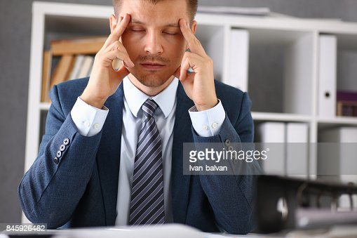 A man experiences stress and a headache in the workplace : Stock Photo