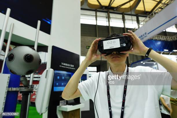 A man experiences virtual reality adopting 5G technology during Mobile World Conference 2017 on June 28 2017 in Shanghai China MWC Shanghai themed on...