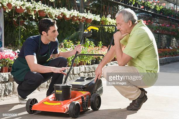 Man explaining about a lawn mower to a customer