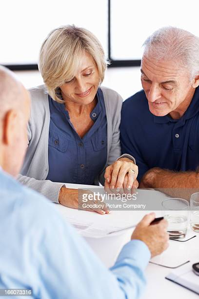 Man explaining investment plans to senior couple