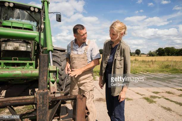 Man explaining woman while standing by agricultural machinery at farm