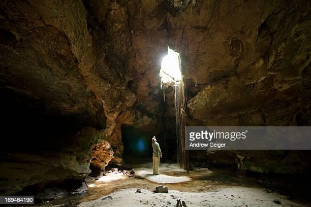 Man exploring cave ceiling waterfall.