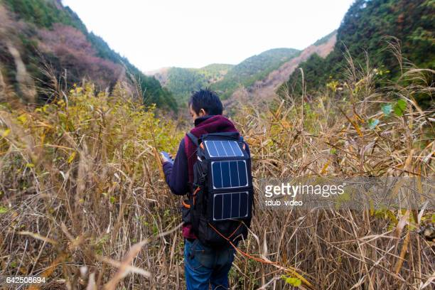 Man exploring thre wilderness with solar powered navigation equipment