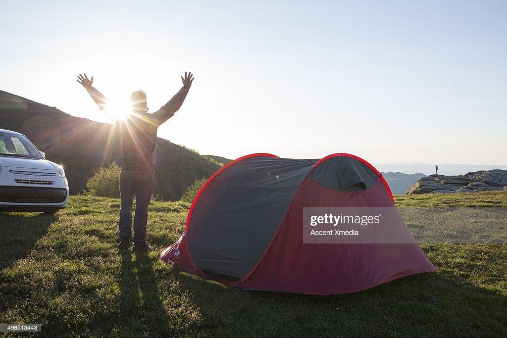Man extends arms at car campsite, sunrise