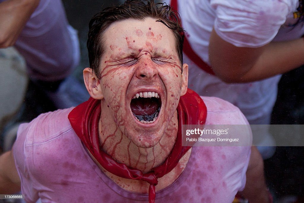A man extends his face sprayed with wine as revellers celebrate during the opening day or 'Chupinazo', of the San Fermin Running of the Bulls fiesta on July 6, 2013 in Pamplona, Spain. The annual Fiesta de San Fermin, made famous by the 1926 novel of US writer Ernest Hemmingway entitled 'The Sun Also Rises,' involves the running of the bulls through the historic heart of Pamplona, this year for nine days from July 6-14.