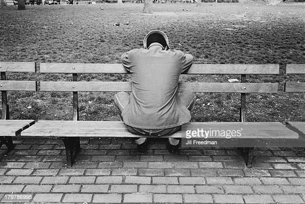 A man faces backwards on a bench in Washington Square Park Greenwich Village New York City 1977