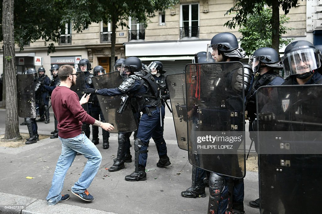 A man faces French anti-riot police during a demonstration against controversial labour reforms, on June 28, 2016 in Paris. Unions have called repeated strikes and marches in opposition to the law, which seeks to bring down France's intractable 10-percent unemployment rate by making it easier to hire and fire workers. / AFP / PHILIPPE