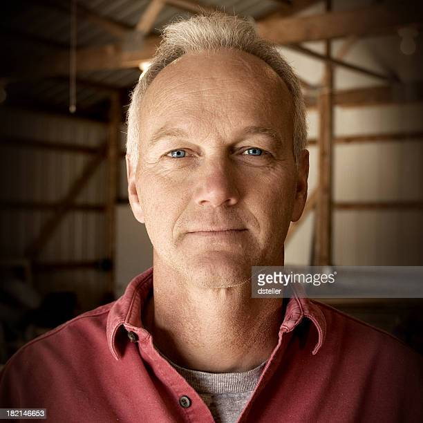 Man facing camera with interior of barn as the background