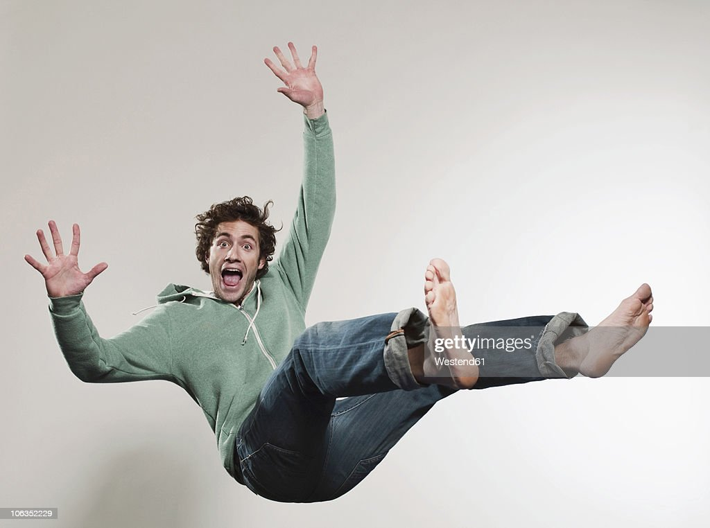 Man falling against grey background, mouth open, portrait