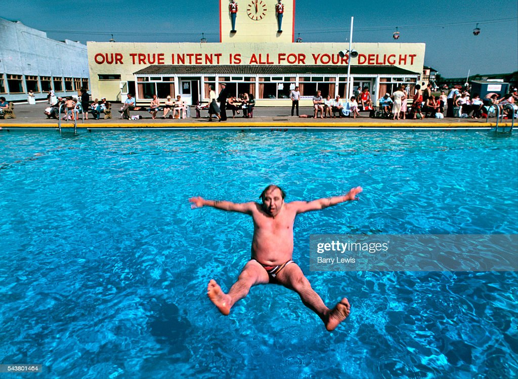 Man falling backwards into swimming pool in Butlins holiday camp, Skegness. The slogan 'Our true intent is all for your delight' was borrowed from Midsummers Night's Dream. Butlins Skegness is a holiday camp located in Ingoldmells near Skegness in Lincolnshire. Sir William Butlin conceived of its creation based on his experiences at a Canadian summer camp in his youth and by observation of the actions of other holiday accommodation providers, both in seaside resort lodging houses and in earlier smaller holiday campsThe camp began opened in 1936, when it quickly proved to be a success with a need for expansion. The camp included dining and recreation facilities, such as dance halls and sports fields. Over the past 75 years the camp has seen continuous use and development, in the mid-1980s and again in the late 1990s being subject to substantial investment and redevelopment. In the late 1990s the site was re-branded as a holiday resort, and remains open today as one of three remaining Butlins resorts.