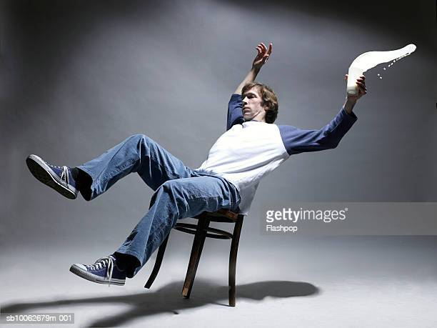Man falling from chair holding glass of milk