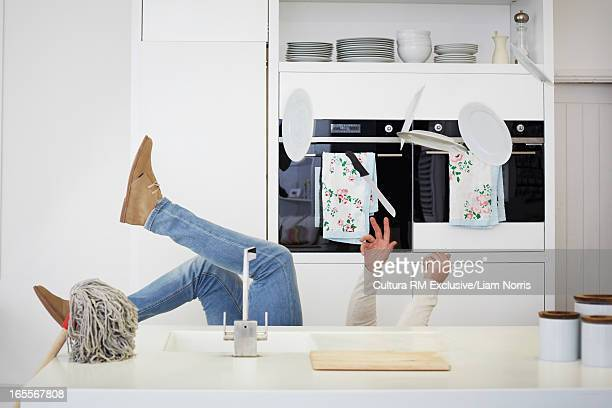 Man falling with dishes in kitchen