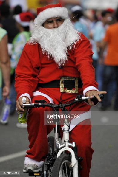 A man fancydressed as Santa Claus rides his bicycle with other hundreds along the streets of Cali deparment of Valle del Cauca Colombia on December...