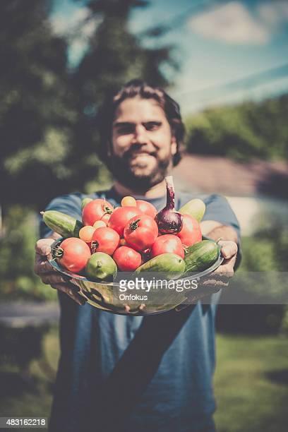 Man Farmer Holding Bowl full of Vegetables