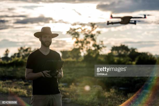 Man Farmer Pilot Using Drone Remote Controller at Sunset