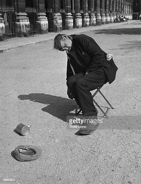 A man fast asleep on a stool in the court of the Palais Royal in Paris