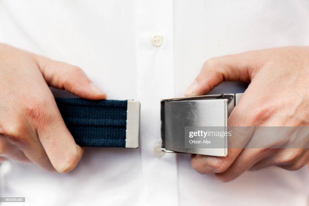 Man fastening seat belt on airplane