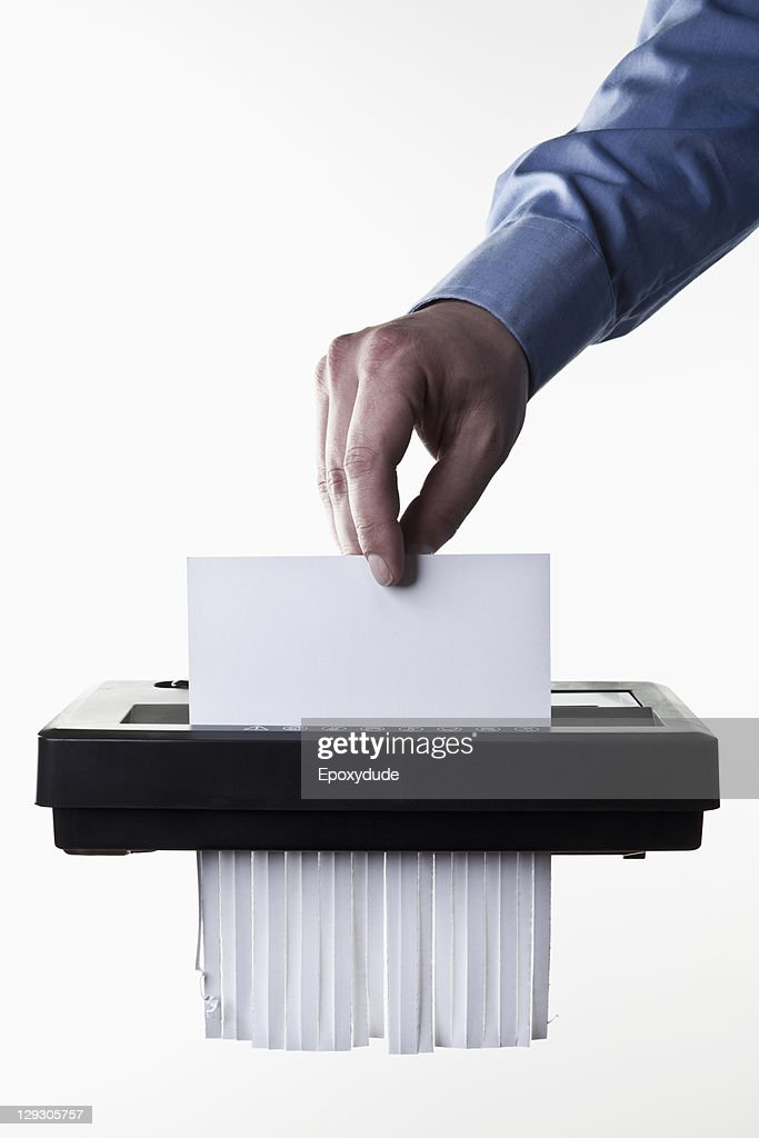 A man feeding a blank document into a paper shredder, close-up