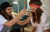 Man feeding blindfolded woman, smiling