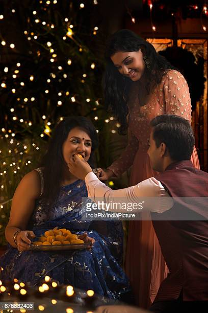 Man feeding laddoo to his mother on diwali festival