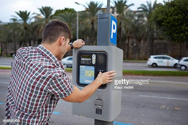 Man feeding parking meter