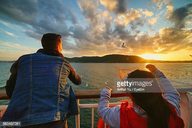 Man Feeding Seagull With His Daughter From Yacht Railing