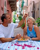 Man feeding spaghetti to woman at restaurant